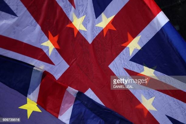 TOPSHOT AntiBrexit demonstrators wave a European Union flag and a Union flag in the rain outside the Houses of Parliament in London on March 29 2018...