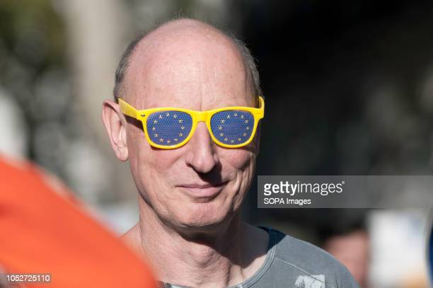 AntiBrexit protester seen with yellow sun glasses with blue stars emulating the European Union flag during the march A huge demonstration organised...
