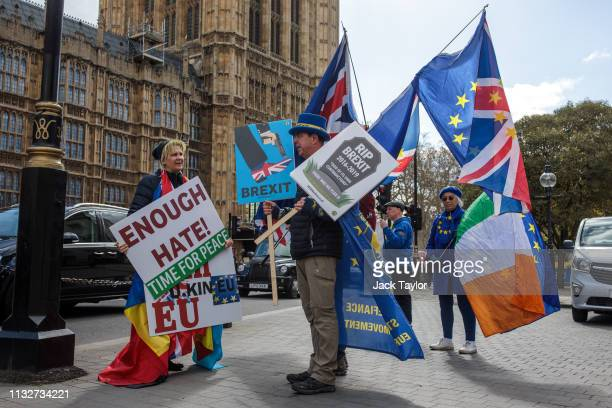AntiBrexit protesters demonstrate with flags outside the Houses of Parliament on March 25 2019 in London England British Prime Minister Theresa May...