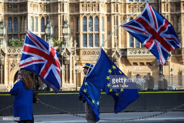 Antibrexit protesters wave Union Jack and EU flags outside the Houses of Parliament on December 8 2017 in London England British Prime Minister...