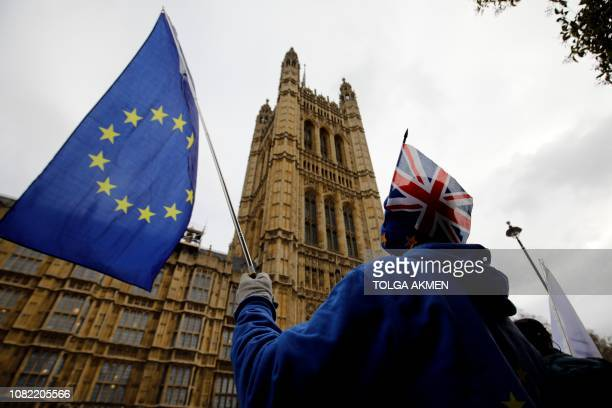 AntiBrexit supporters hold placards and flags as they demonstrate outside the Houses of Parliament on January 14 2019 Prime Minister Theresa May...
