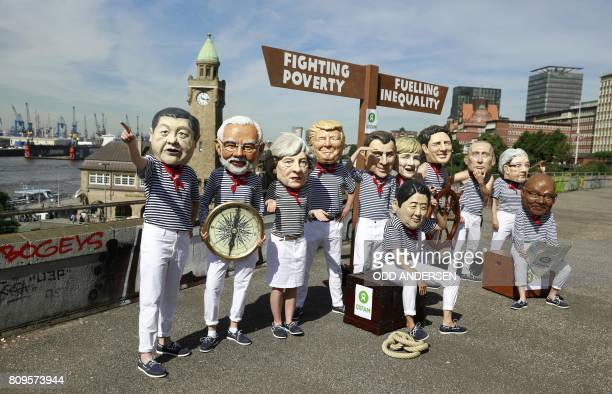 Anticapitalism activists wearing masks featuring China's President Xi Jinping India's Prime Minister Narendra Modi Britain's Prime Minister Theresa...