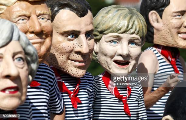 Anticapitalism activists wearing masks of Britain's Prime Minister Theresa May US President Donald Trump French President Emmanuel Macron German...