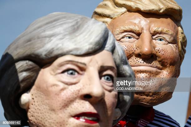 Anticapitalism activists wearing masks of Britain's Prime Minister Theresa May and US President Donald Trump protest on July 6 2017 in Hamburg...