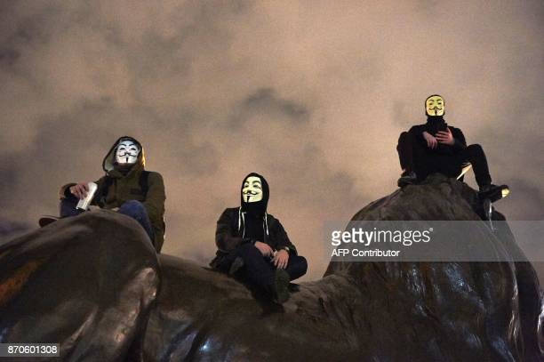 Anticapitalist demonstrators sit on statues as they gather in Trafalgar Square during the 'Million Masks March' organised by the group Anonymous in...