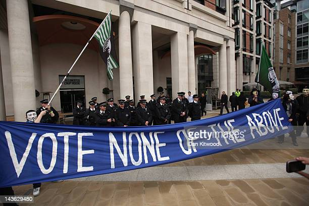 Anticapitalist protesters from the 'Occupy' movement hold a banner in front of police officers ahead of a demonstration on May 1 2012 in London...
