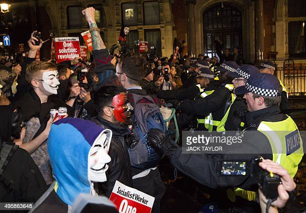 Anticapitalist protesters wearing Guy Fawkes masks clash with British police officers during the 'Million Masks March' organised by the group...