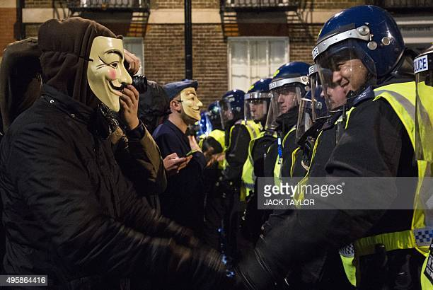 """Anti-capitalist protesters wearing Guy Fawkes masks clash with British police during the """"Million Masks March"""", organised by the group Anonymous,..."""