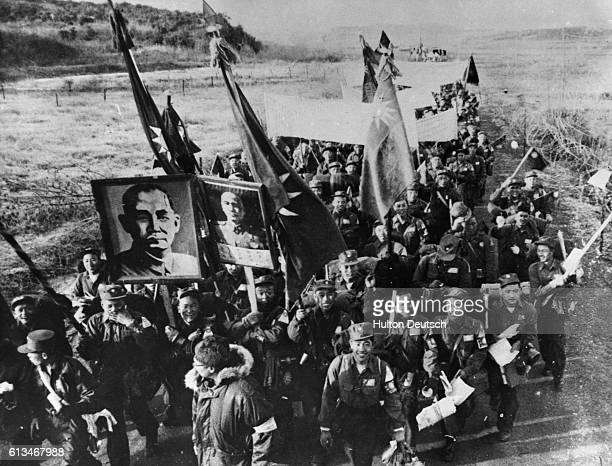 Anticommunist Chinese prisoners of the Korean War march along a road to Inchon where they will be taken to Taiwan They carry Chinese Nationalist...