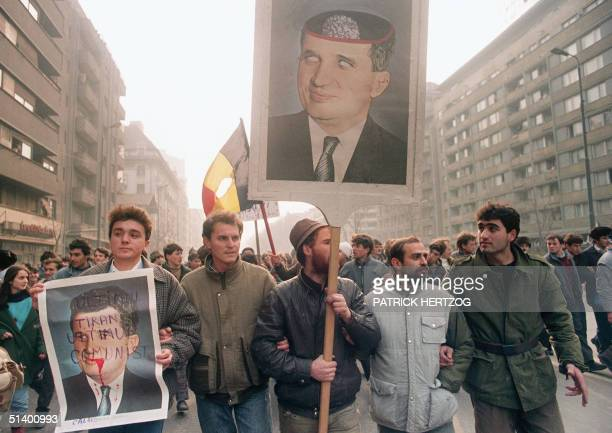 AntiCommunist civilians hold antiCeausescu portraits 25 December 1989 in downtown Bucharest as the antiCommunist uprising to end Nicolae Ceausescu's...