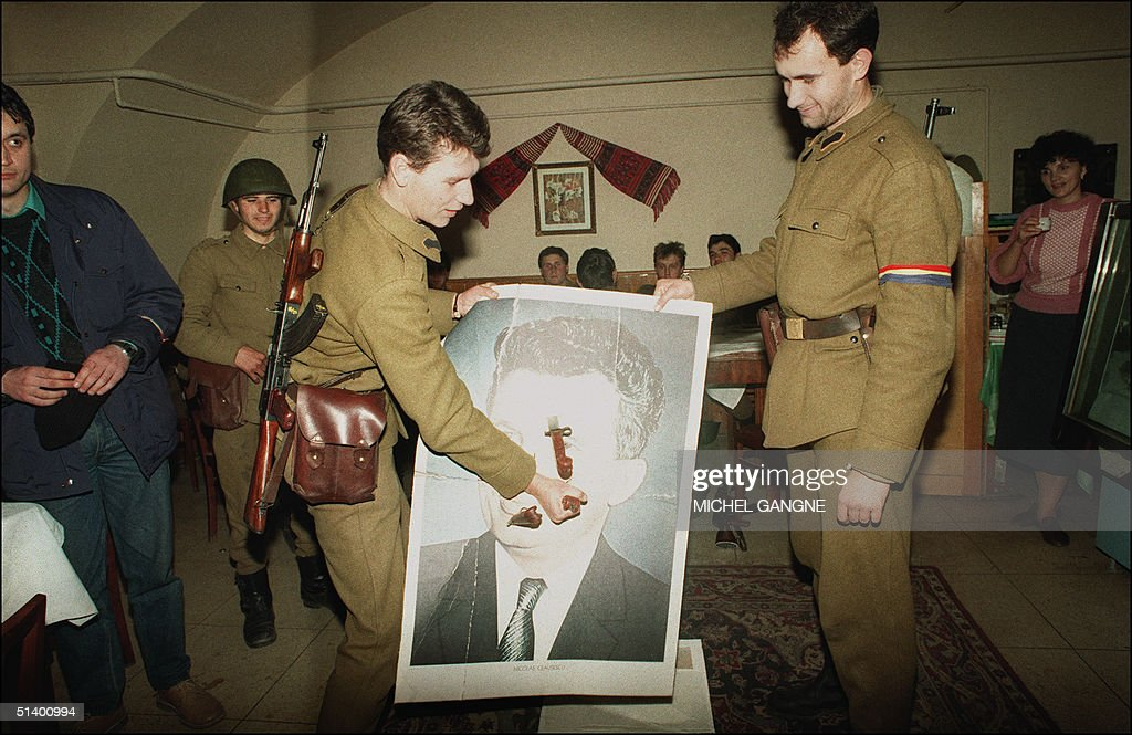 Anti-Communist soldier (L) sticks a bayonet through a portrait of late Romanian Communist leader Nicolae Ceausescu 28 December 1989 in Sibiu as the anti-Communist uprising to end Nicolae Ceausescu's 24 years of dictatorial rule continue. The communist dictator N. Ceausescu and his wife Elena were deposed and executed by a firing squad 25 December 1989. Eight years after the December 1989 revolution which toppled Ceausescu, Romania has begun lifting the veil on the 'mysteries' surrounding the uprising and the circumstances which brought former president Ion Iliescu to power. According to general prosecutor Sorin Moisescu, reports put about at the time of 'terrorists loyal to Ceausescu' provoking bloody diversions to sow panic in the population, were 'fabricated' to justify Iliescu's takeover. 'Nothing that happened after 22 December 1989 was due to chance. The deaths of some of the demonstrators were supposed to provide legitimacy to the new regime' Moisecu said 24 December 1998.