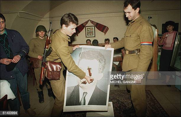 AntiCommunist soldier sticks a bayonet through a portrait of late Romanian Communist leader Nicolae Ceausescu 28 December 1989 in Sibiu as the...