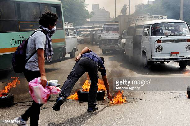 Anticoup Egyptian students stand behind the burning tyres during an anticoup protest outside Cairo University in Giza Egypt on October 22 2014