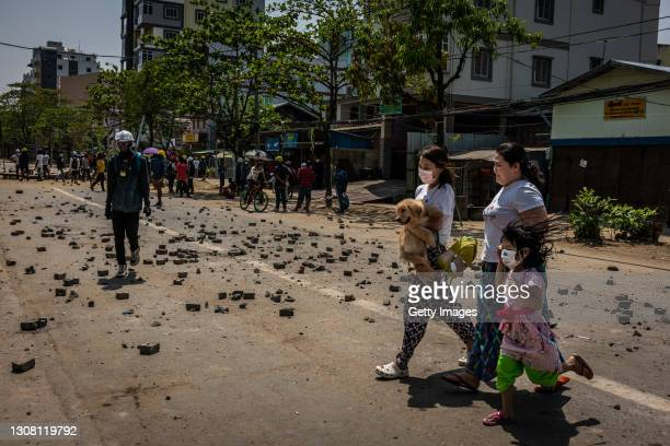 Anti-coup protesters A woman carries her dog as her family crosses a front line between protesters and military junta forces on March 20, 2021 in...