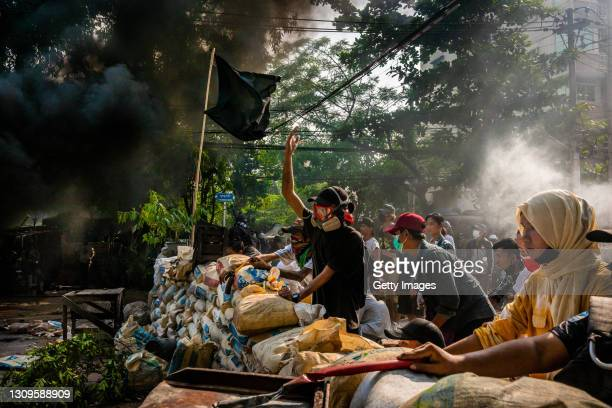 Anti-coup protesters shout slogans towards approaching security forces as smoke rises from burning car tires on March 28, 2021 in Yangon, Myanmar....