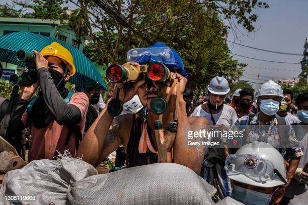 Anti-coup protesters use binoculars to spot military junta forces on March 20, 2021 in Yangon, Myanmar. Myanmar's military Junta charged deposed...
