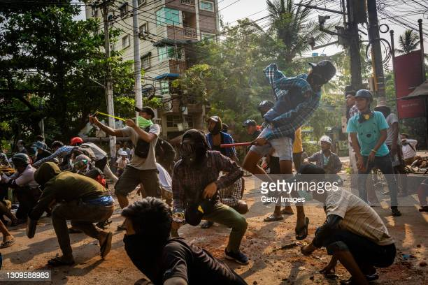Anti-coup protesters use slingshots and pelt stones towards approaching security forces on March 28, 2021 in Yangon, Myanmar. Myanmar's military...
