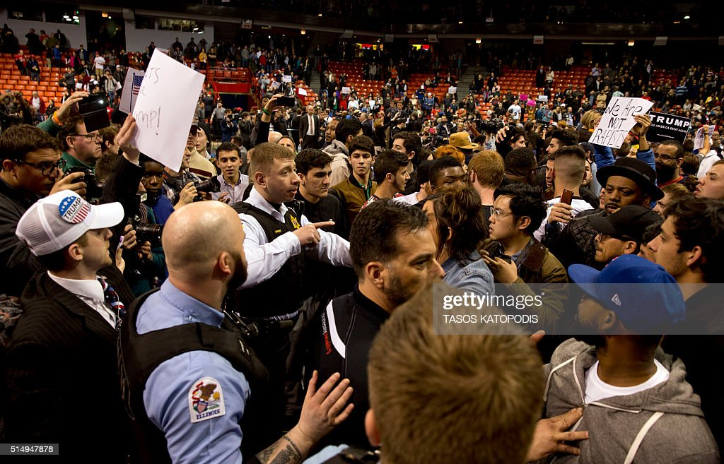 Anti-Donald Trump protesters confront with his supporters during a Trump rally at the UIC Pavilion in Chicago on March 11, 2016. Republican White House hopeful Donald Trump cancelled his appearance at a Chicago rally Friday amid extraordinary scenes of chaos, with hundreds of protesters clashing with the frontrunner's supporters and police struggling to maintain order. / AFP / Tasos KATOPODIS