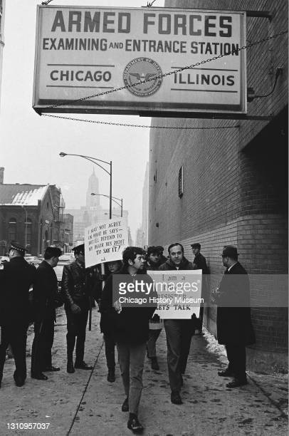 Anti-draft and anti-war protesters demonstrating outside the Armed Forces induction center at 615 West Van Buren Street, Chicago, Illinois, and the...