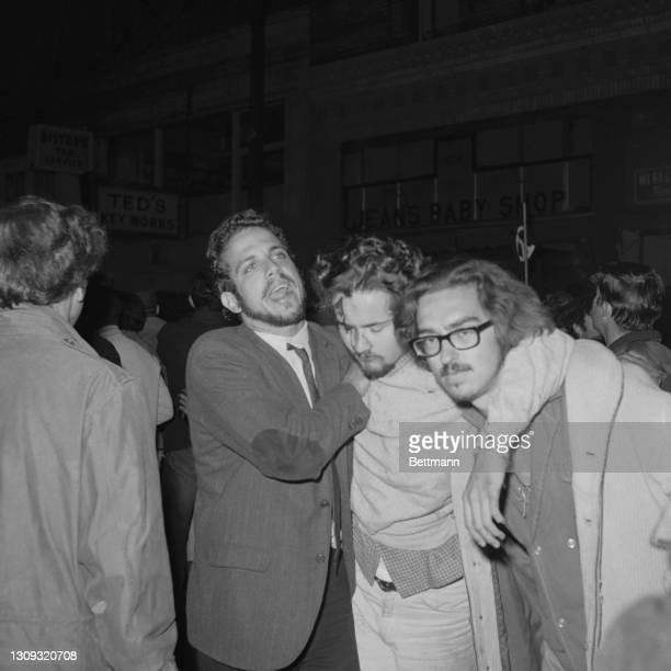 Anti-draft demonstrator, injured by club-swinging police, is aided by anguished friends. Squads of police, winging clubs and firing cannisters of eye...