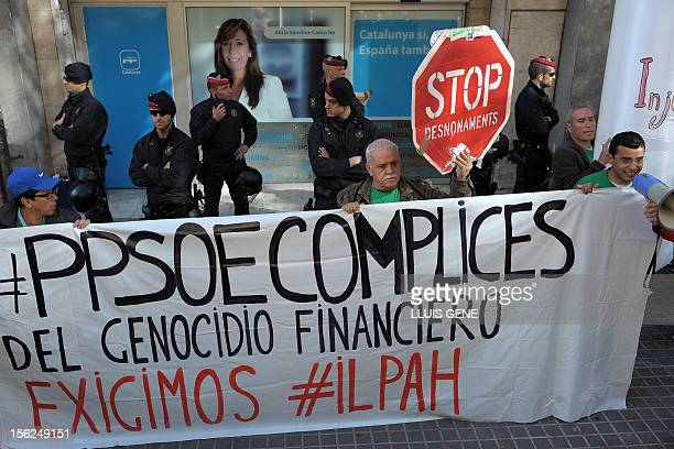 """Anti-eviction activists hold a placard reading """"PPSOE accomplices of the financial genocide"""" as they take part in a protest against evictions in..."""