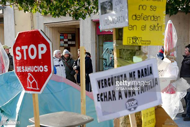 Anti-eviction activists take part in a demonstration in front of a Caja Laboral bank succursal in Burgos, on March 14, 2013. Homeowners ruined by...