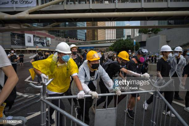 Antiextradition protesters push barricades on a street during a standoff outside the Legislative Council Complex ahead of the annual flag raising...