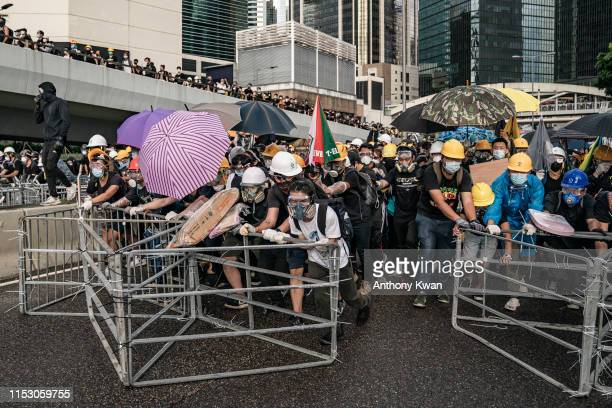 Antiextradition protesters push barricades toward police on a street during a standoff outside the Legislative Council Complex ahead of the annual...