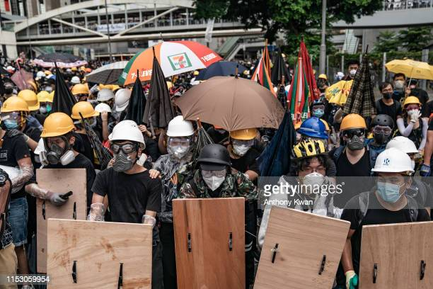 Antiextradition protesters use makeshift shield to defend themselves during a clash with police outside the Legislative Council Complex ahead of the...