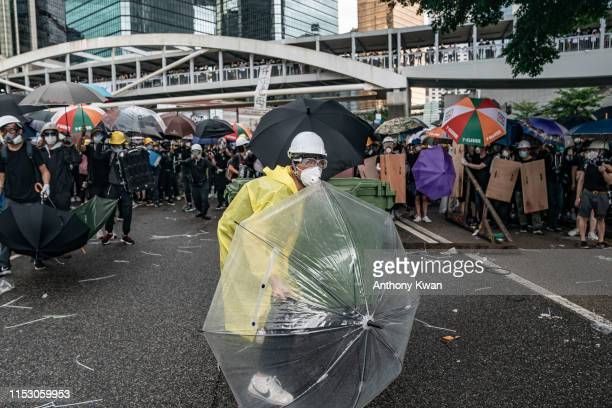 Antiextradition protesters use umbrellas to defend themselves during a clash with police outside the Legislative Council Complex ahead of the annual...
