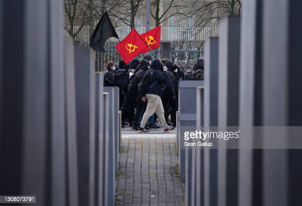 Antifa and leftist protesters carry communist flags as they march past the Holocaust Memorial while demonstrating against gatherings of neo-Nazis...