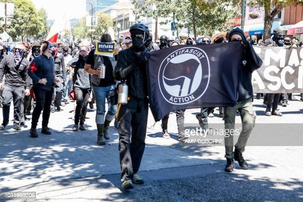 Antifa militants march with counter protesters as they protest an altright rally on August 5 2018 in downtown Berkeley California