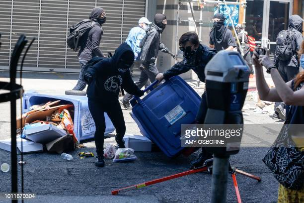 Antifa militants use fencing and trash cans to protect themselves from the smoke bombs shot at them and counter protesters by the police on August 5...