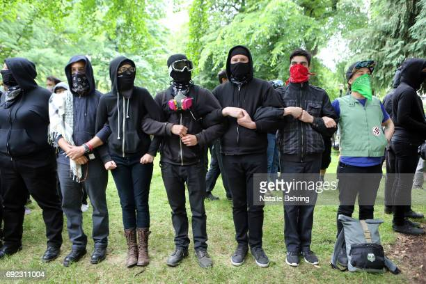 'Antifa' protesters link arms as they demonstrate at a rally on June 4 2017 in Portland Oregon A protest dubbed 'Trump Free Speech' by organizers was...
