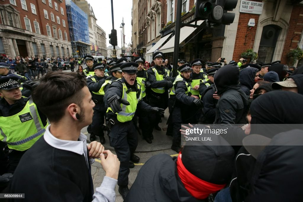 TOPSHOT - Anti-facist activists clash with police as they counter protest against marches by the far-right English Defence League and Britain First in central London on April 1, 2017. Members of the Britain First group and the English Defence League rallied in central London in on seperate marches entitled a 'March Against Terrorism' and 'We Are Not Afraid' following the terror attack on Westminster Bridge and the British Parliament on March 22 which killed four people. The marches were opposed by the Unite Against Fascism organisation who held a static demonstration against the other groups. / AFP PHOTO / Daniel LEAL