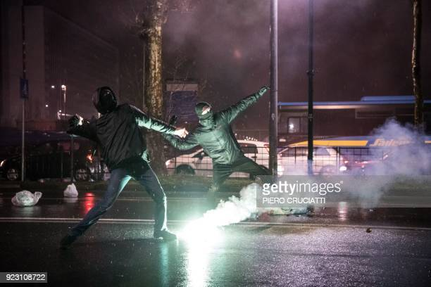 Antifascist activists throw bottles at police officers during a rally against an election campaign meeting organized by far-right movement CasaPound...