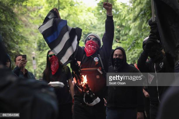 Antifascist demonstrators burn a blue lives matter flag during a protest on June 4 2017 in Portland Oregon A protest dubbed Trump Free Speech by...