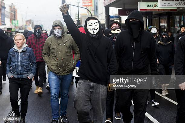 Antifascist protestors wearing masks and hooded tops march down the main street in coburg as a man in a guy fawkes mask clenches his fist in the air...