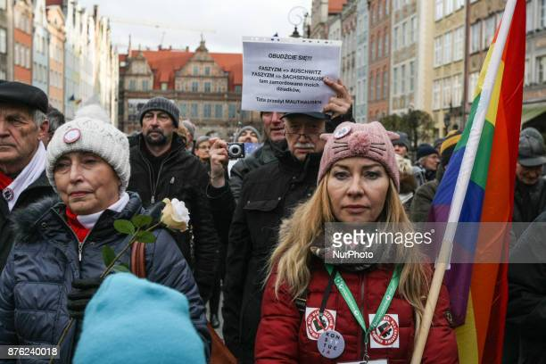 Antifascist rally participants with banner that speaks Wake Up fascism is Auschwitz fascism is Sachsenhausen My grandparents were murdered there my...