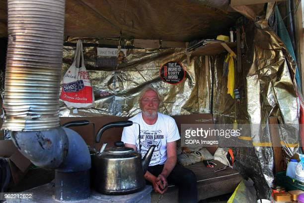 AntiFrack Protestor Tom sits in a hut setup to protect protesters from the weather on the roadside at the Fracking company Cuadrilla's Frack site...