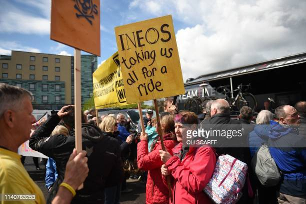 AntiFracking demonstrators protest by cycling team Team Ineos in advance of the first stage of the Tour de Yorkshire in Doncaster north England on...