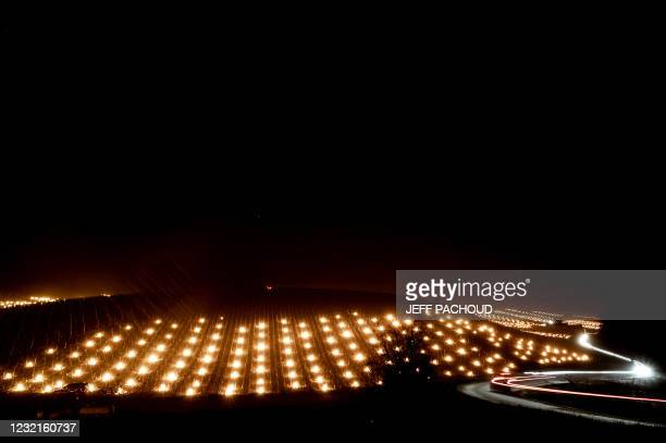 Anti-frost candles burn in the Chablis vineyards near Chablis, Burgundy, on April 7, 2021 as temperatures fall below zero degrees celsius during the...
