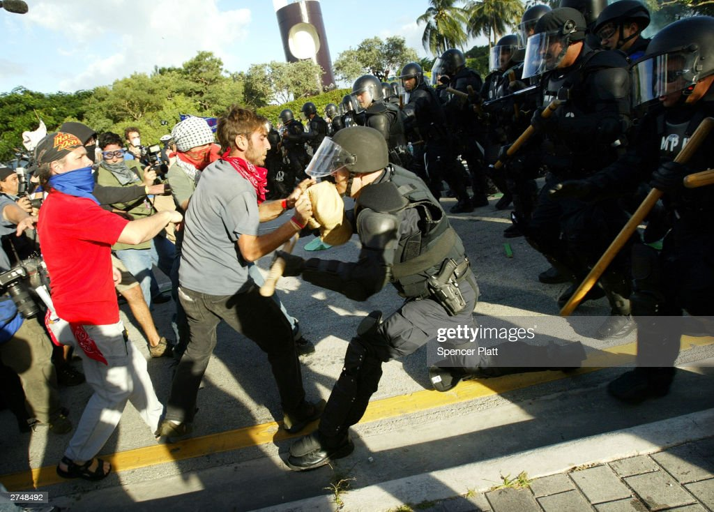 Anti-globalization protesters clash with police in riot gear on the fourth day of the summit to create a Free Trade Area of the Americas November 20, 2003 in Miami, Florida. Hundreds of protesters, including a group of anarchists, clashed with police throughout the morning as they unsuccessfully tried to make their way to the Hotel Inter-Continental where the summit was taking place. Protesters say the pact would damage the environment, exploit workers overseas and cost many Americans their jobs.