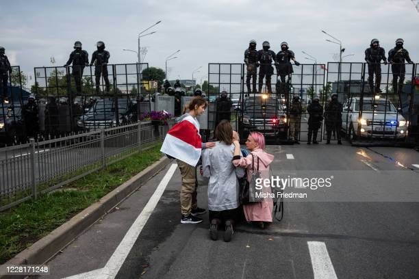 Anti-goverment protestors console a praying woman near riot police on August 23, 2020 in Minsk, Belarus. There have been near daily demonstrations...