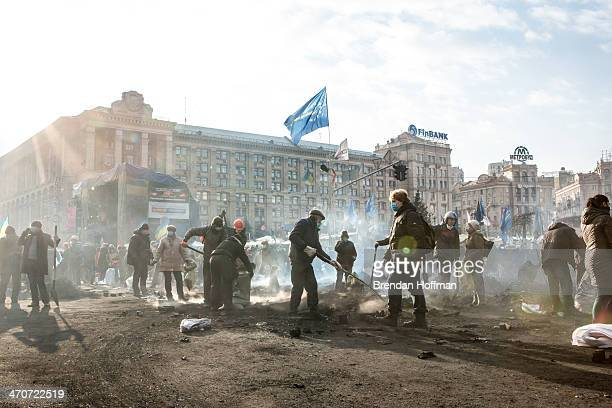 Antigovernent protesters clear ashes and debris from a newly occupied portion of Independence Square on February 20 2014 in Kiev Ukraine Dozens of...