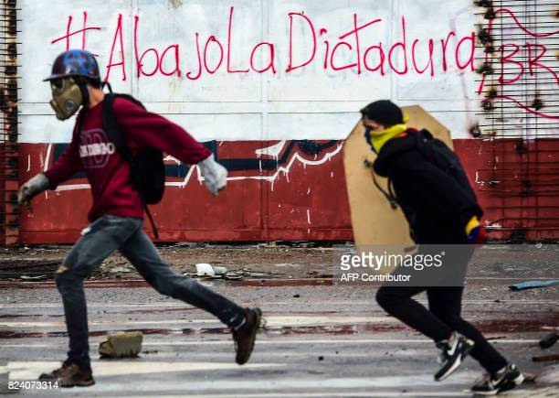 Antigovernment activists clash with riot police during a protest in Caracas on July 28 2017 Protesters took over streets in Caracas on Friday in a...