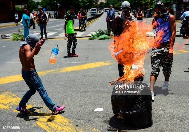 TOPSHOT Antigovernment activists demonstrate against Venezuelan President Nicolas Maduro at a barricade set up on a road in Caracas on August 8 2017...