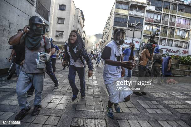 Antigovernment activists scatter upon being charged by riot police during a protest against the election of a Constituent Assembly proposed by...