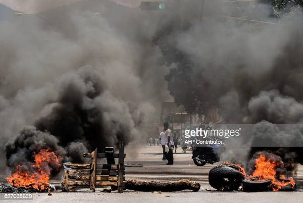 Antigovernment activists stand near a barricade burning in flames in Venezuela's third city Valencia on August 6 a day after a new assembly with...