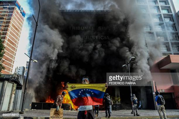 TOPSHOT Antigovernment demonstrators attack the administration headquarters of the Supreme Court of Justice as part of protests against President...